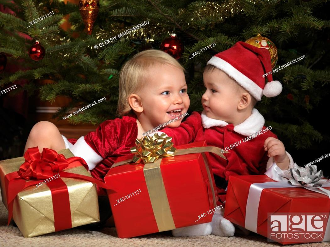 Stock Photo: Two year old girl and an eight month old boy sharing gifts under a Christmas tree.