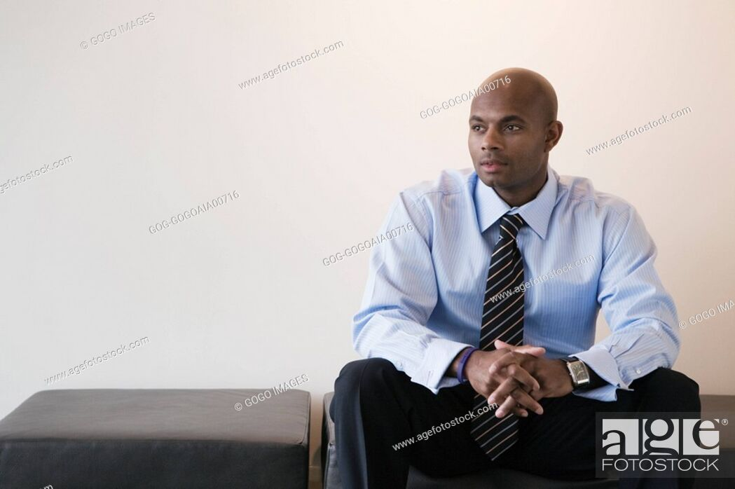 Stock Photo: African businessman sitting on bench.
