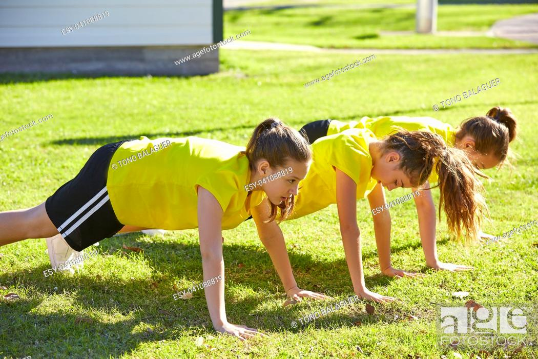 Stock Photo: Friend girls teens push up push-ups workout ABS in a park turf grass.