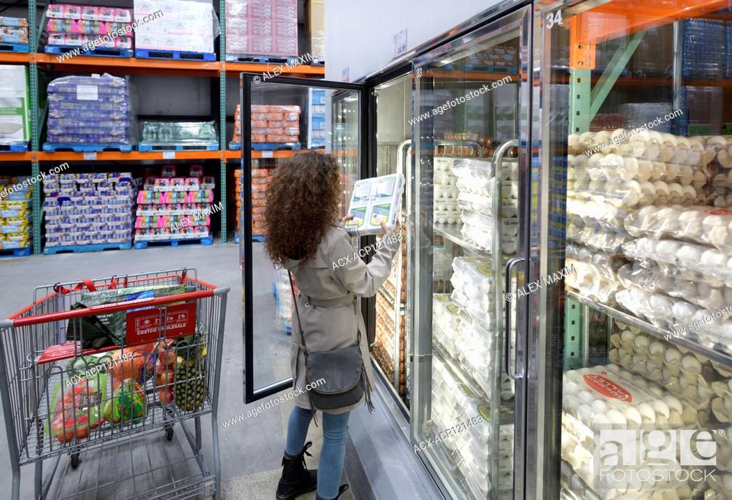Imagen: Woman picking a crate of omega-3 eggs from a fridge at Costco Wholesale membership warehouse store food section. British Columbia, Canada 2017.
