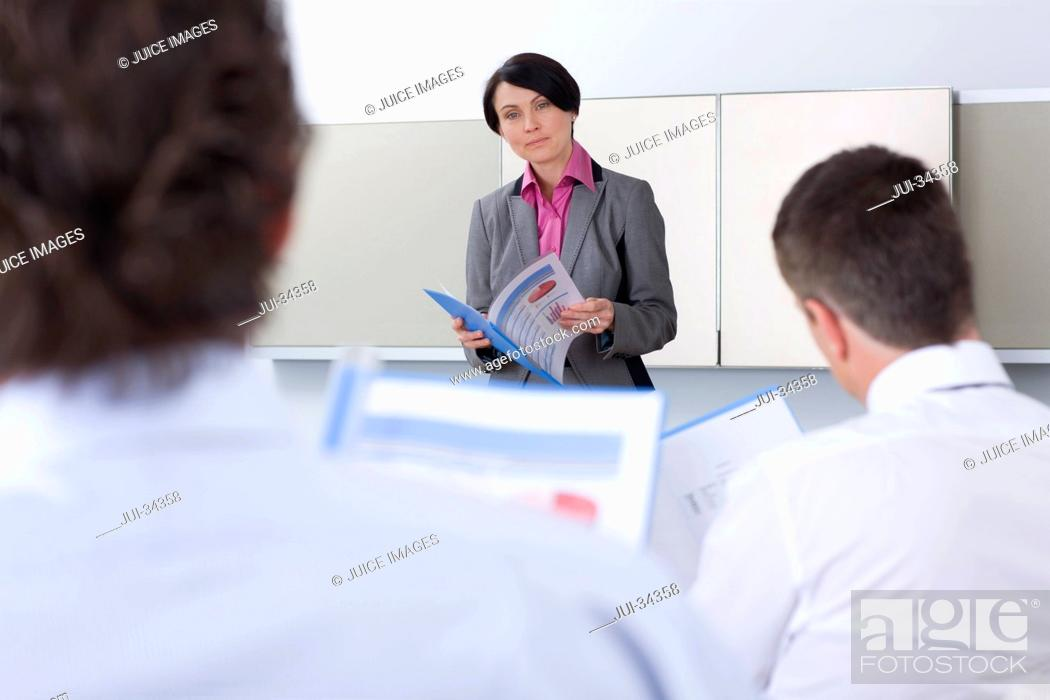 Stock Photo: Businesswoman holding report and leading meeting in conference room.