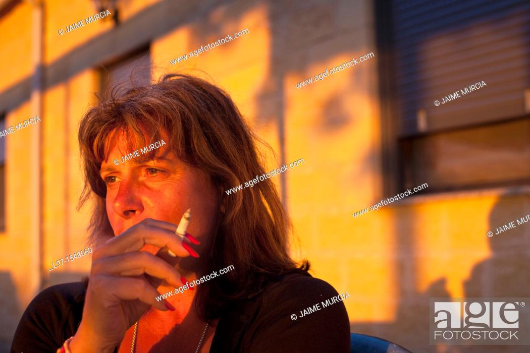 Stock Photo: Woman relaxing in the evening sunlight with a cigarette.