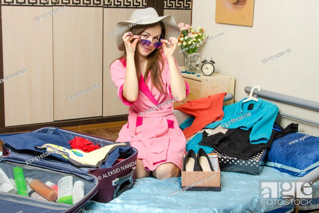 Stock Photo: The girl in a dressing gown collects things for the ride.