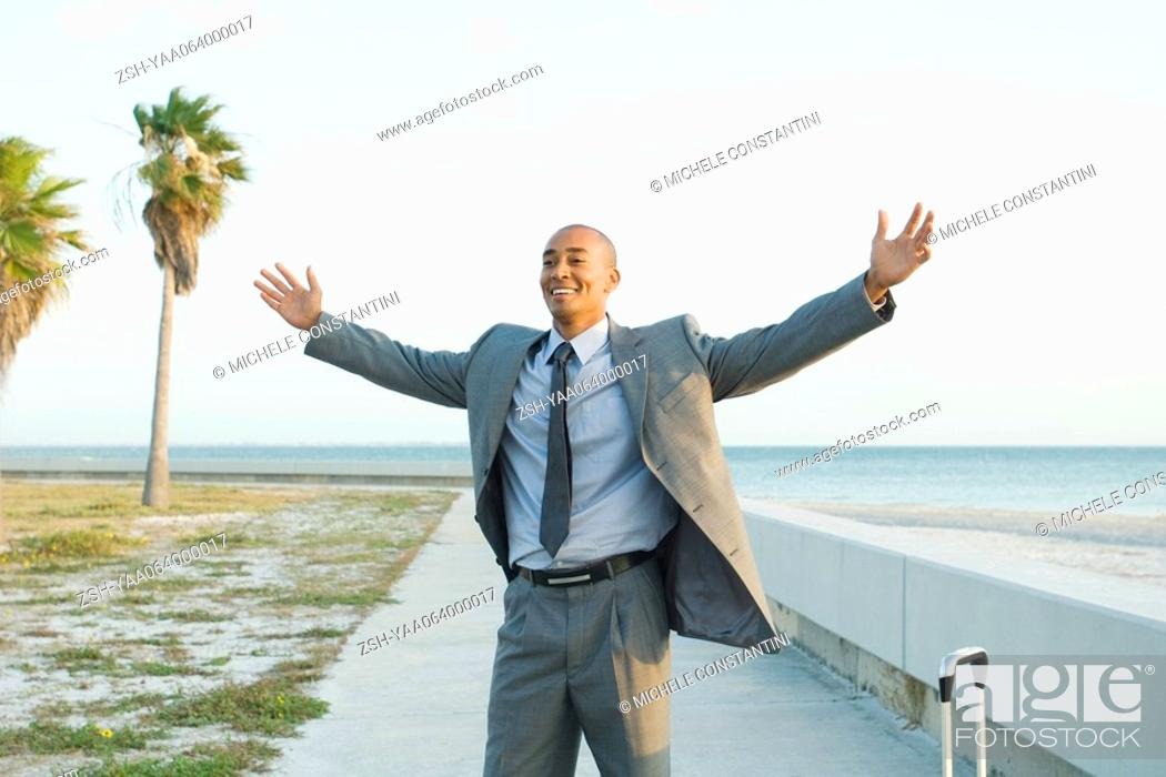 Stock Photo: Businessman standing near beach with arms raised, smiling.