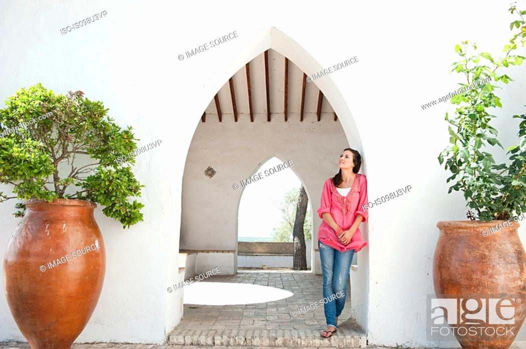 Stock Photo: Young woman standing by archway.