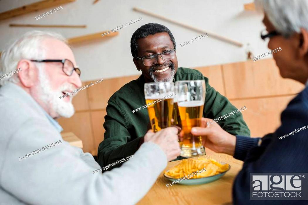 Stock Photo: group of smiling senior friends clinking glasses of beer in bar.