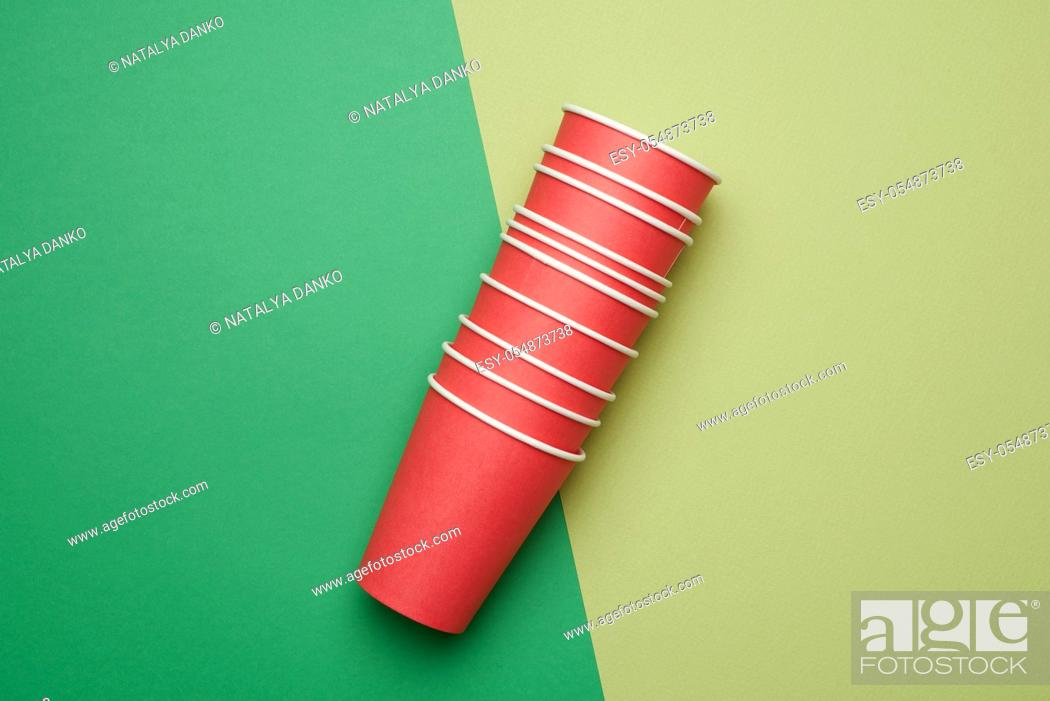 Stock Photo: stack of red paper disposable cups on a green background, flat lay, concept eco-friendly, zero waste.