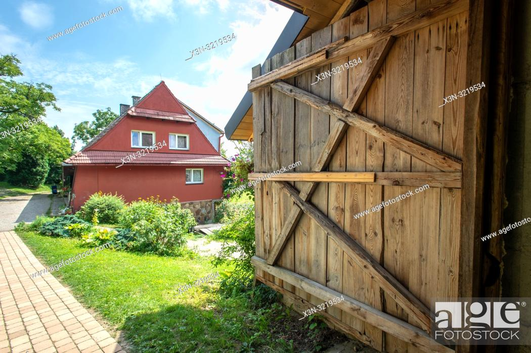 Stock Photo: Wooden door and a small pathway leading to a red farm cottage with gardens. Glich—w, Lesser Poland Voivodeship, Poland.
