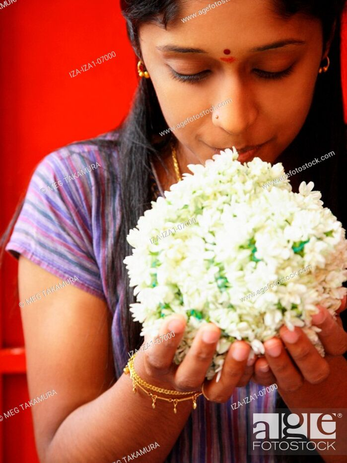Imagen: Close-up of a young woman smelling flowers.