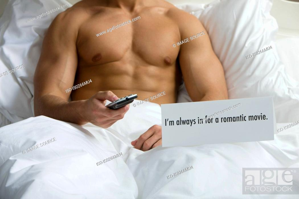 Stock Photo: A man watching tv in bed.