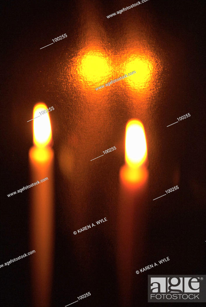 Stock Photo: Two candles and their reflections surrounded by darkness.