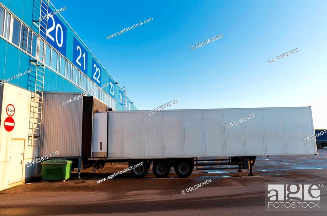 Stock Photo: logistic, storage, shipment, transportation and loading concept - warehouse gate and truck loading.