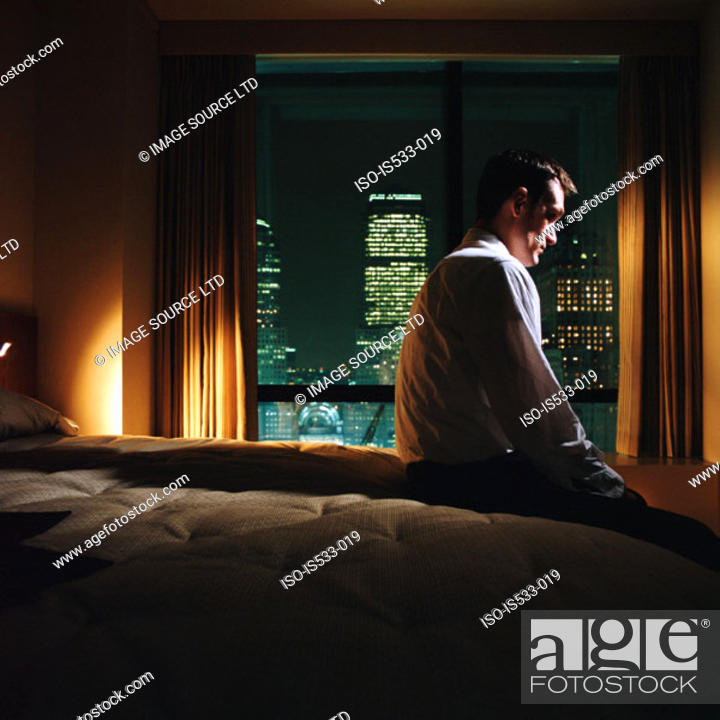 Stock Photo: Serious looking man sitting on bed.