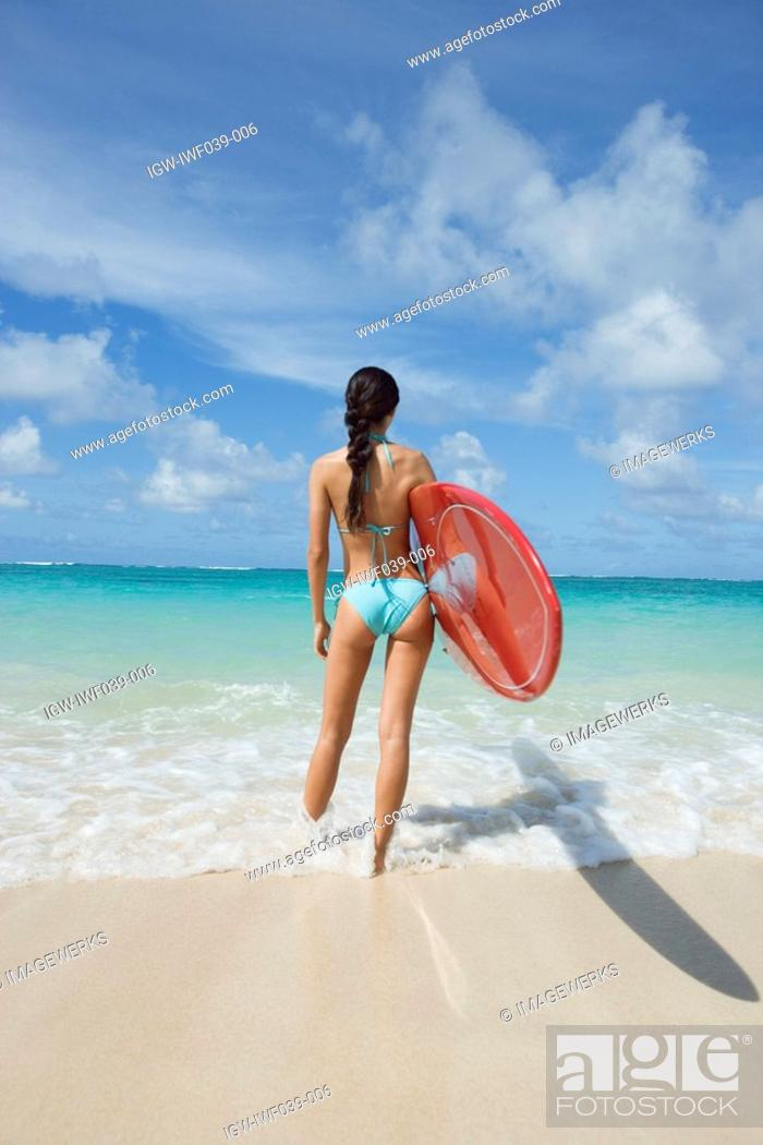 Stock Photo: A woman standing on beach with surfboard in hand.