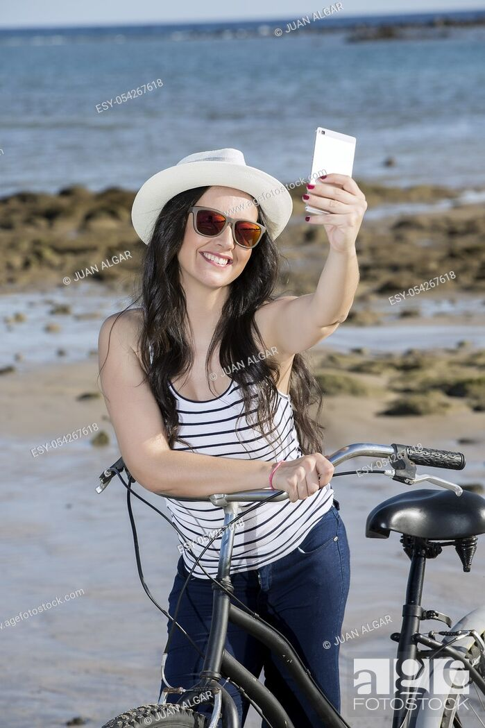 Stock Photo: Young smiley woman in hat and sunglasses with bike getting selfie on seaside of Gran Canaria, Spain.