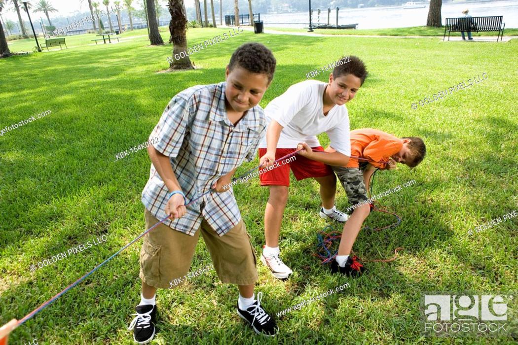 Stock Photo: Three boys pulling hard at a tug-of-war.