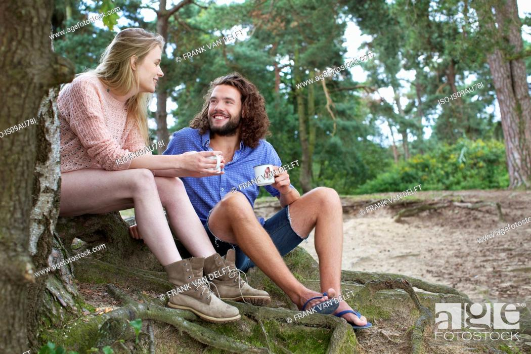 Stock Photo: Young couple chatting beside tree.