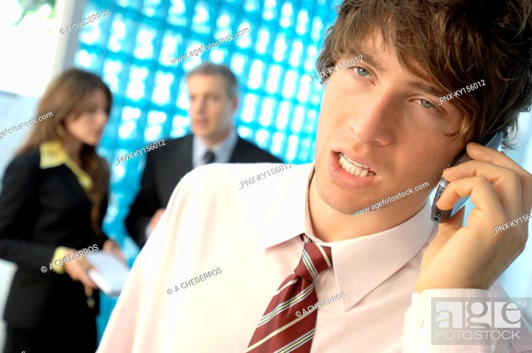 Stock Photo: Businessman using mobile phone with colleagues in background.
