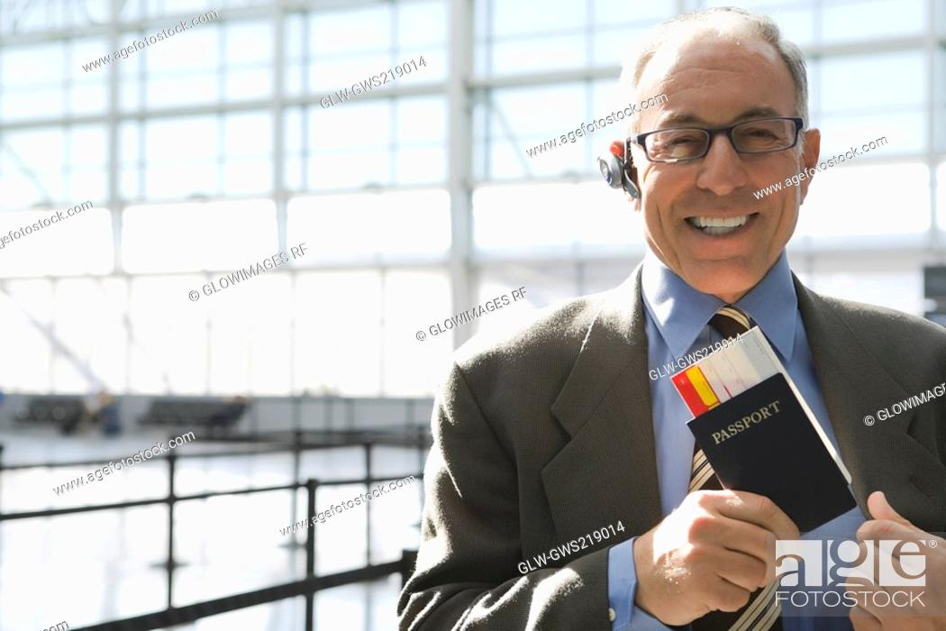 Stock Photo: Portrait of a businessman putting a passport with an airplane ticket in his coat's pocket.