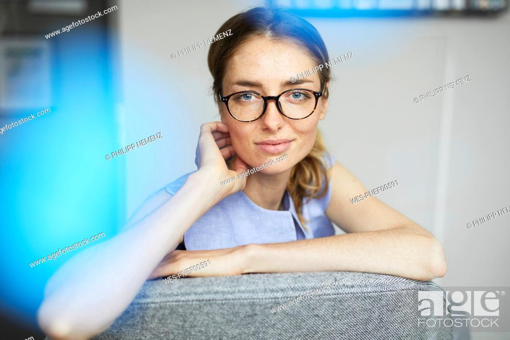 Stock Photo: Portrait of smiling woman wearing glasses sitting on armchair.