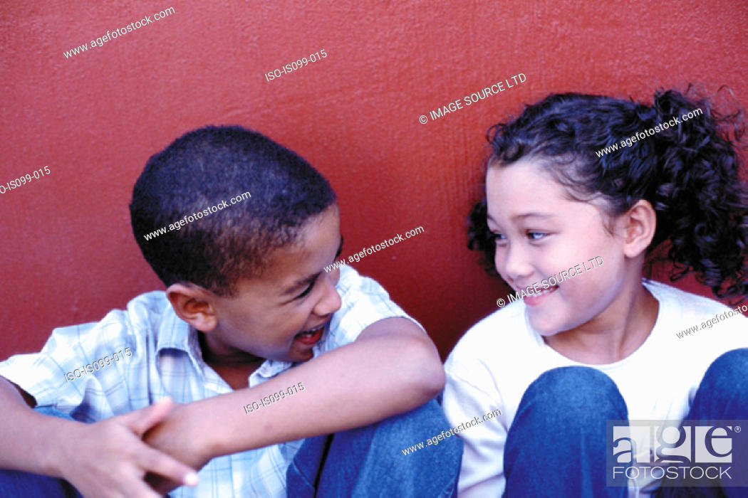 Stock Photo: Boy and girl against wall.