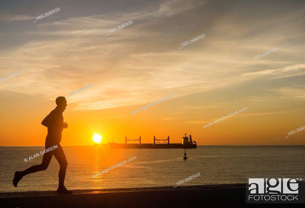 Stock Photo: A jogger on sea wall as the sun rises over the Atlantic Ocean from Avenida Maritima in Las Palmas, Gran Canaria, Canary Islands, Spain,.
