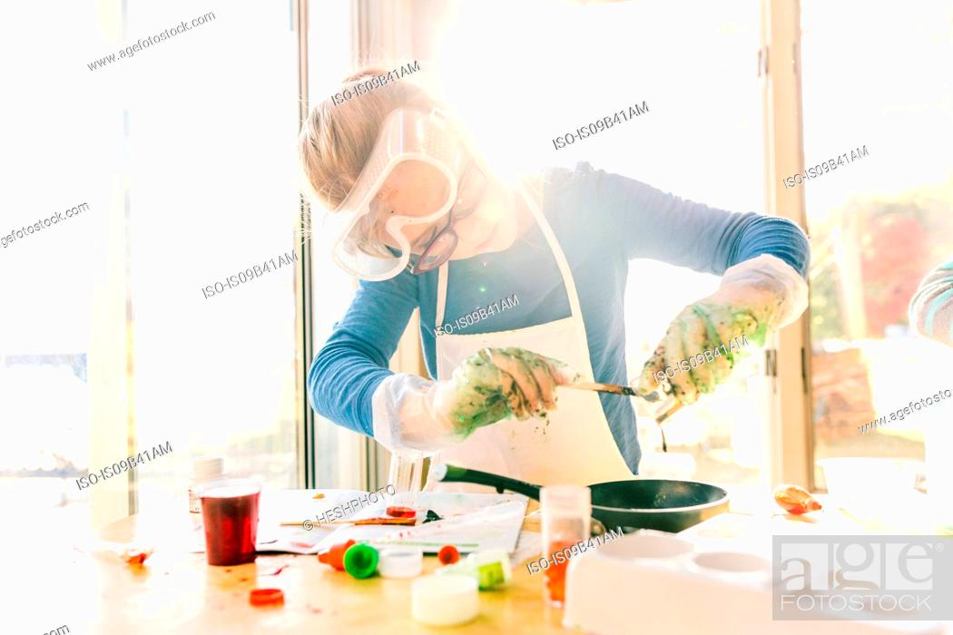 Stock Photo: Girl doing science experiment, pouring green liquid into frying pan.