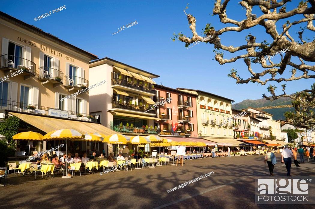 Stock Photo: People passing pavement cafe of the Restaurant and Hotel Moevenpick Albergo Carcani at harbour promenade, Ascona, Lake Maggiore, Ticino, Switzerland.