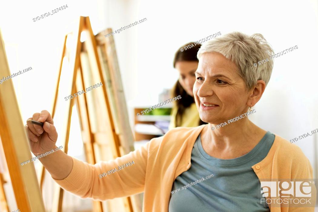 Imagen: senior woman drawing on easel at art school studio.