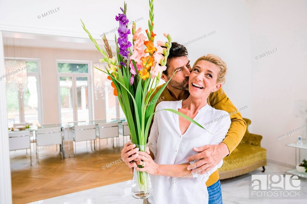 Imagen: Romantic mature man kissing wife on cheek whilst gifting flowers in dining room.