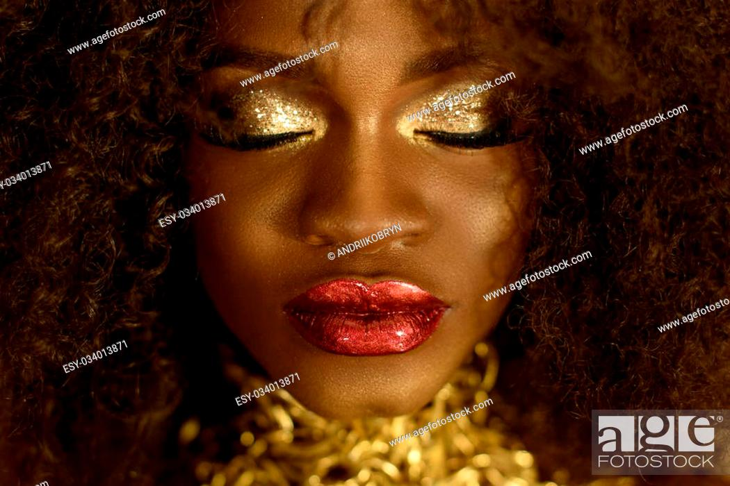 Stock Photo: Surreal close-up portrait of young african american female model with gold glossy makeup. Face art. Fashion concept.