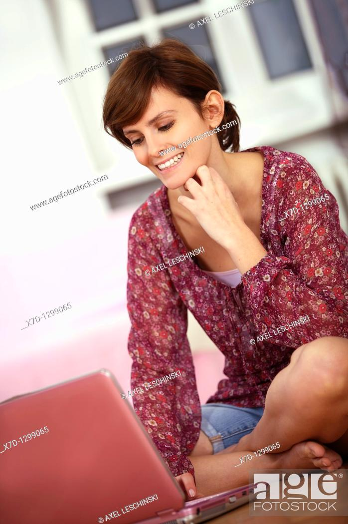 Stock Photo: young woman sitting on floor surfing in the web.