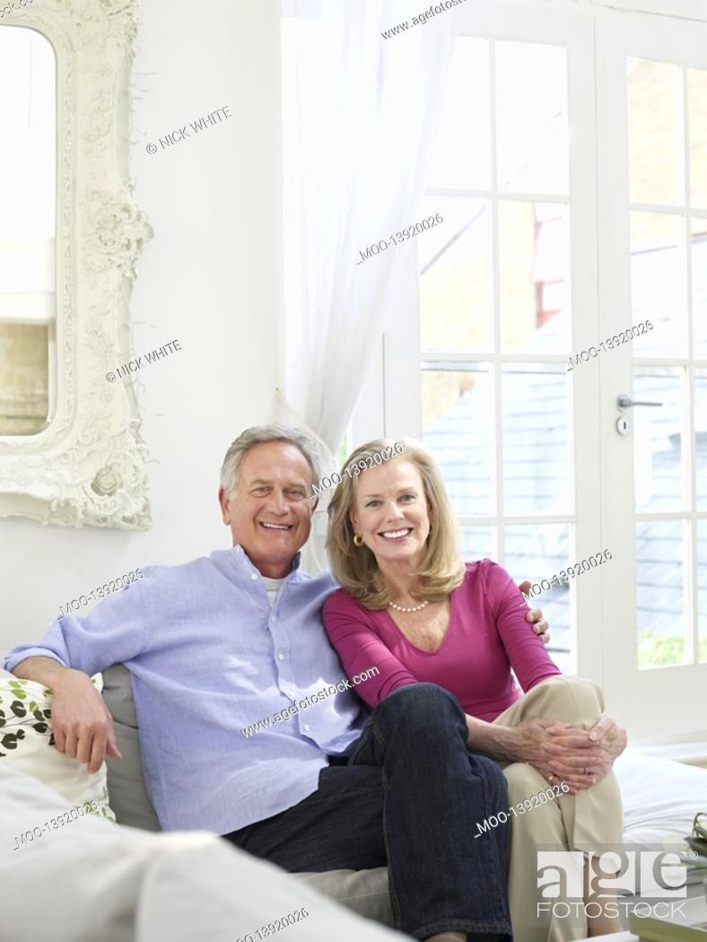 Stock Photo: Senior couple sitting on sofa portrait.