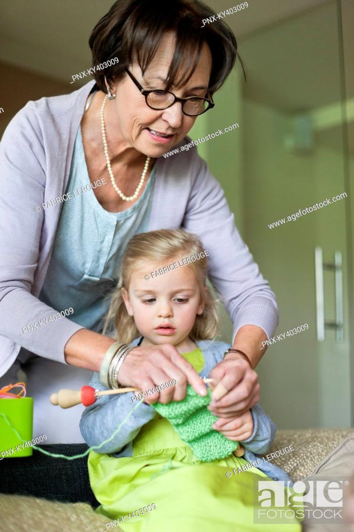 Stock Photo: Little girl learning knitting from her grandmother.