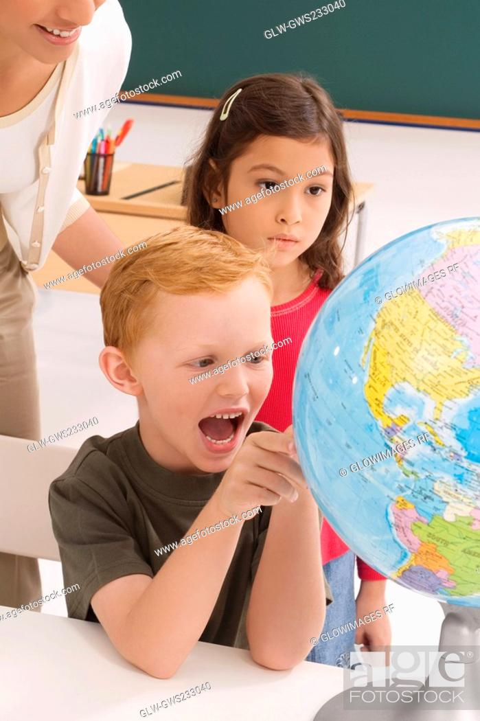 Stock Photo: Schoolboy looking at a globe and shouting with a schoolgirl and a female teacher standing behind him.