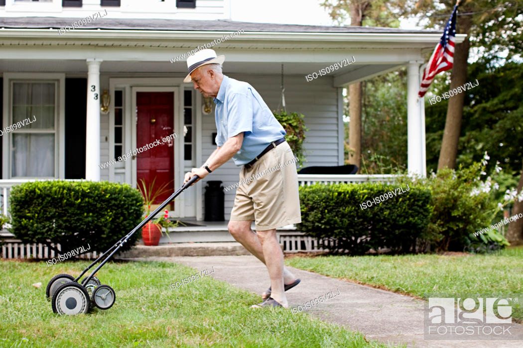 Stock Photo: Senior man mowing his front lawn.