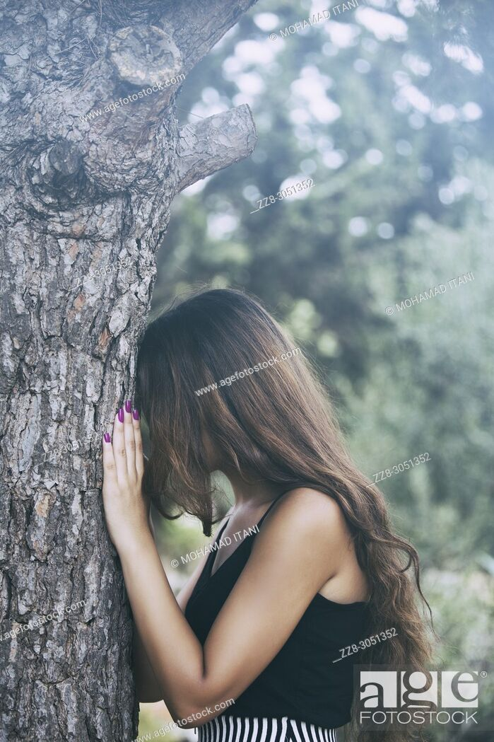 Stock Photo: Depressed young woman leaning against a tree crying.