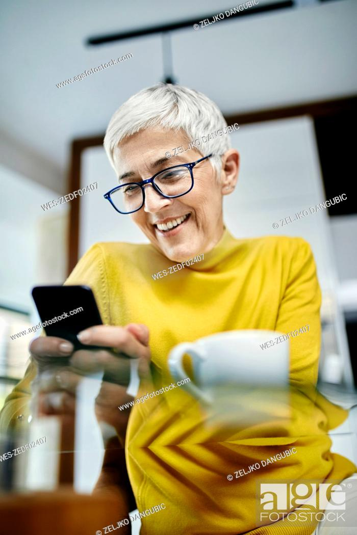 Stock Photo: Senior woman drinking coffee, checking text messages on her smartphone.