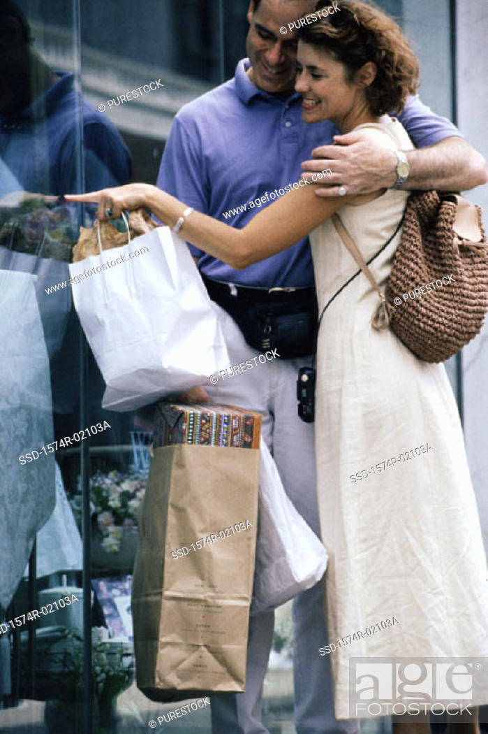 Stock Photo: Young couple looking through a shop window.