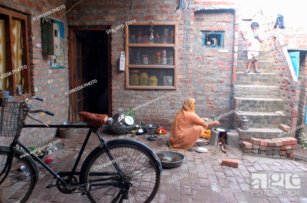 Stock Photo: A Punjaban (word used to describe Punjabi woman) making rotis on the clay choolah in the open kitchen at home ; in Doulo Nangal ; a village near the Beas river.