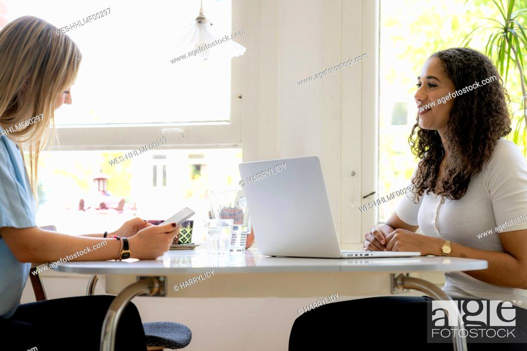 Photo de stock: Two friends working at home together, using laptop.