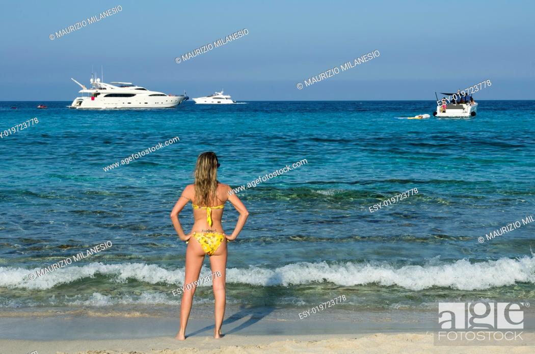 Stock Photo: Blonde girl looking boats on the sea blue and green to the beach.