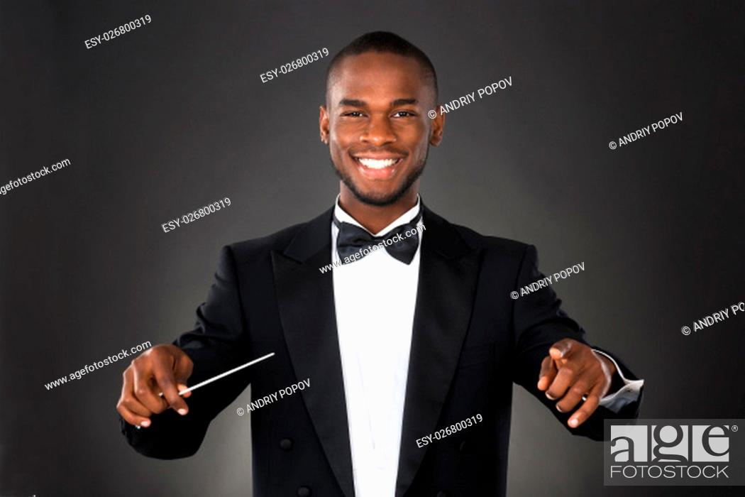Stock Photo: Portrait Of Happy Music Conductor With Baton Against Black Background.