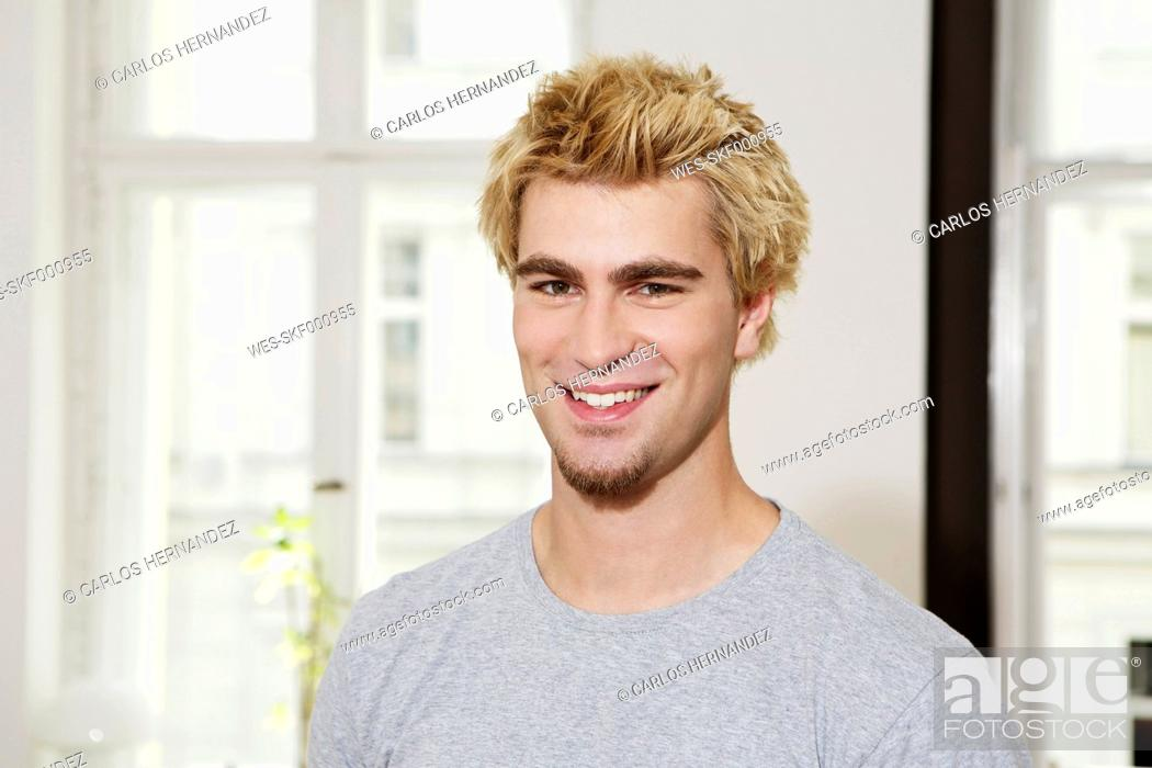 Stock Photo: Germany, Berlin, Young man smiling, portrait.