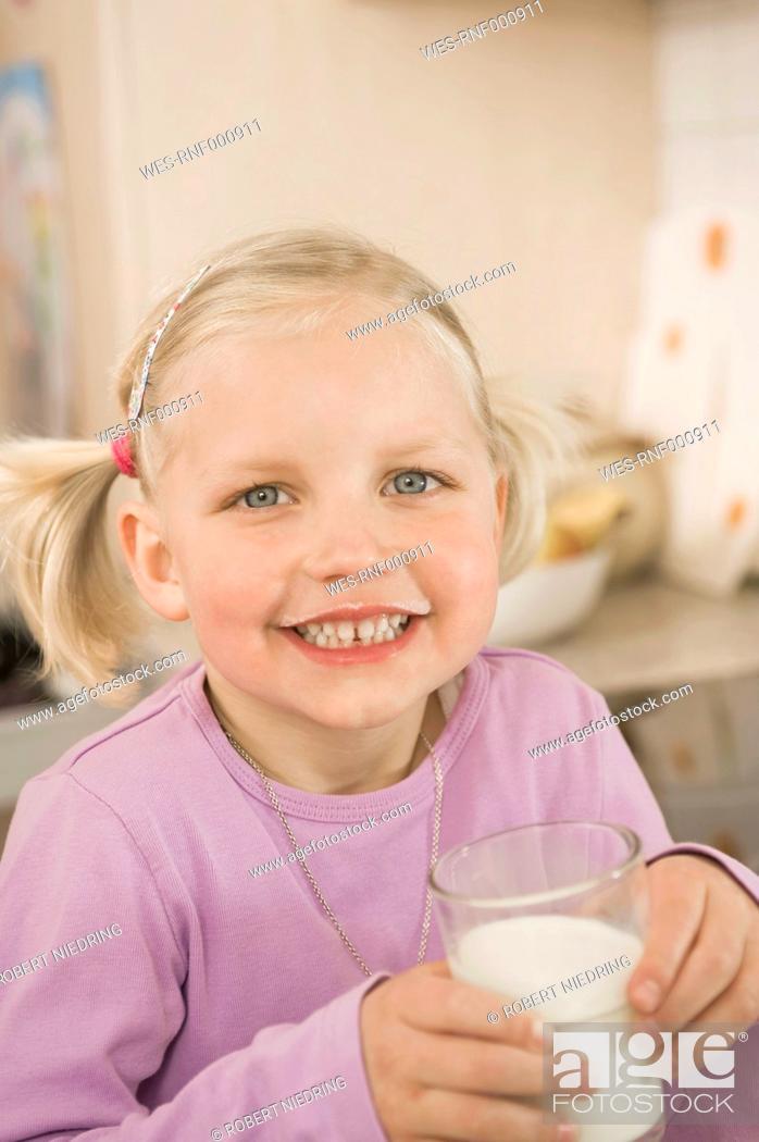 Stock Photo: Girl drinking glass of milk, smiling, portrait.