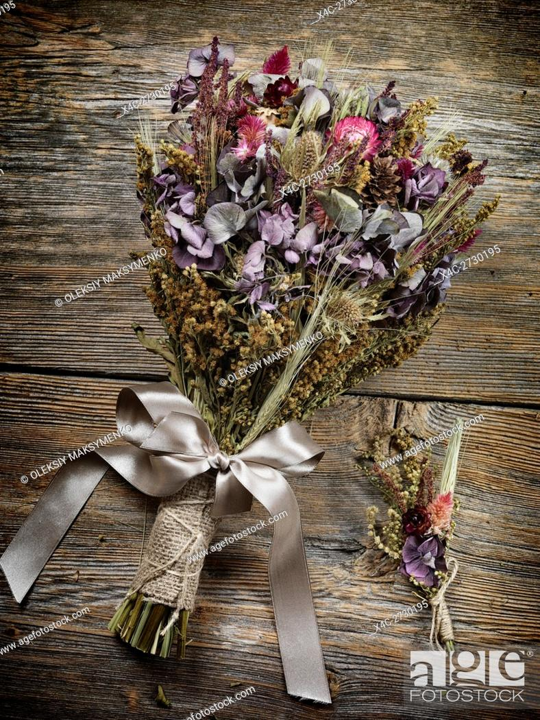 Stock Photo: Rustic country wedding bouquet and boutonniere made of dried wild field flowers, artistic still life.