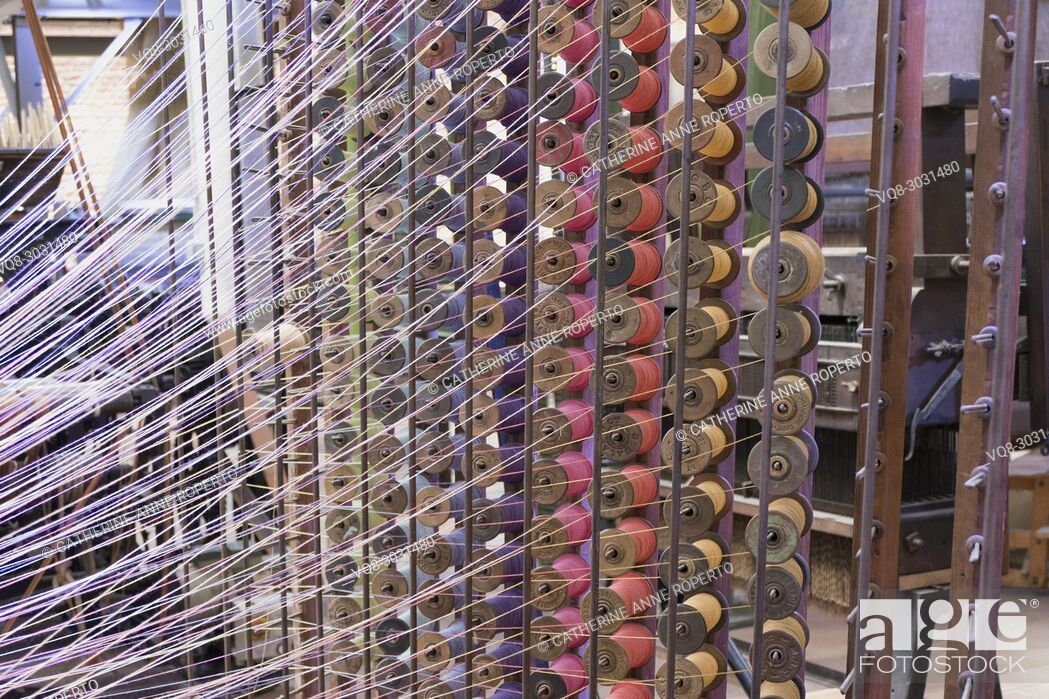 Stock Photo: Dynamically lit skeins of brightly coloured thread on metal racks of wooden spools in traditional jacquard textile weaving, La Manufacture de Roubaix, France.