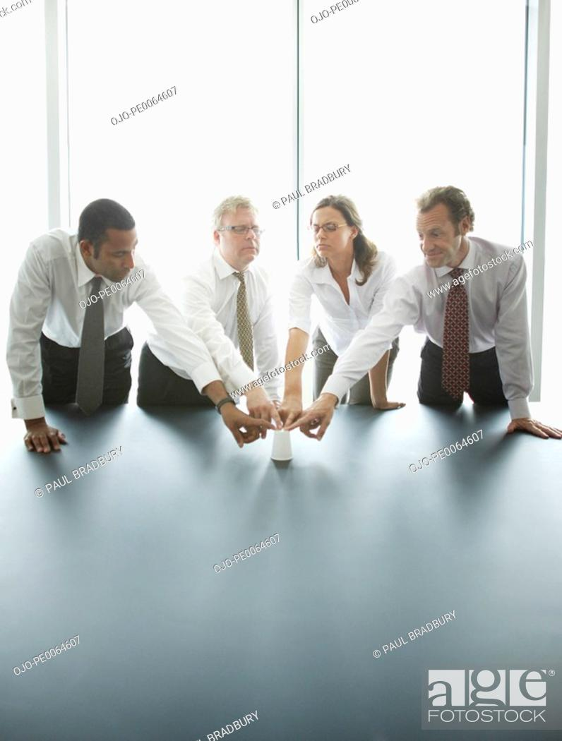 Stock Photo: Businesspeople touching cup together at conference table.
