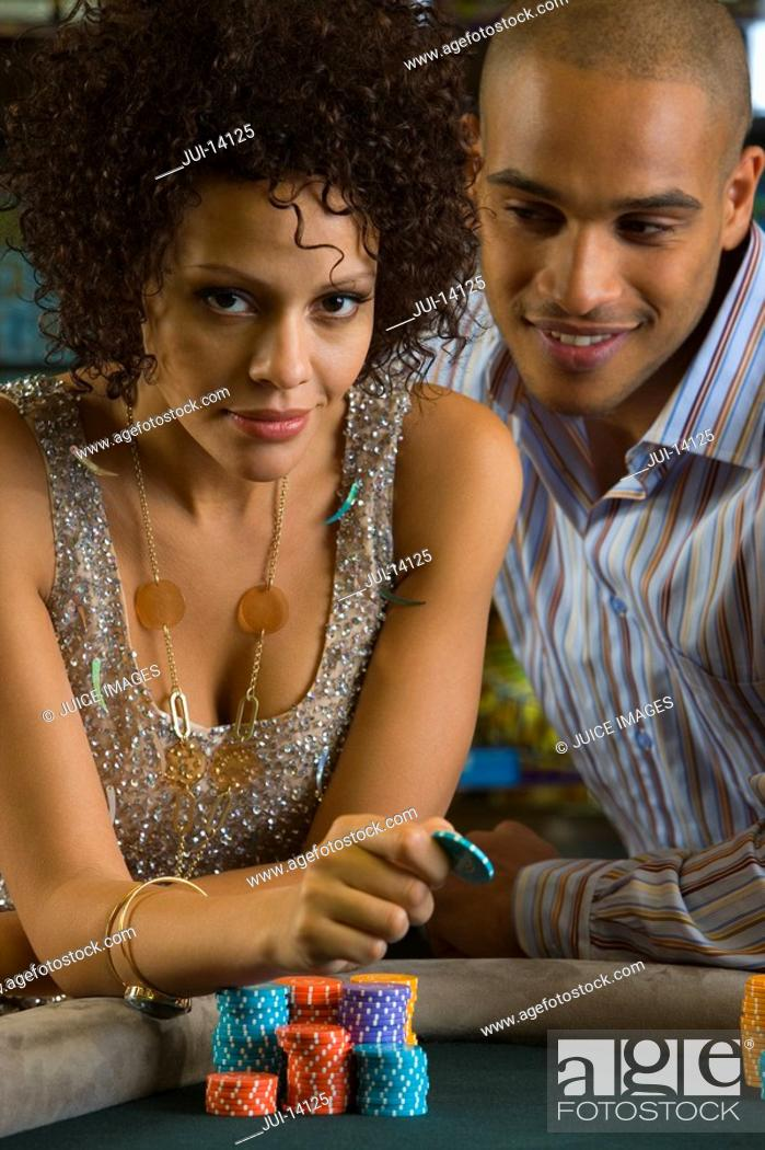Stock Photo: Young couple gambling, woman with gambling chip, portrait.