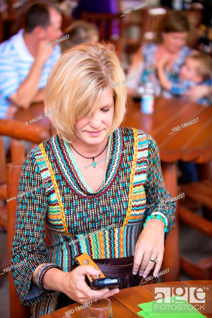 Stock Photo: Caucasian woman in her 40s sending a text message on her smartphone while sitting at a restaurant table.